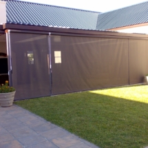 Drop Blind screen in white Sunworker openweave fabric with side track system and protective cassette for the fabric when stored in winter